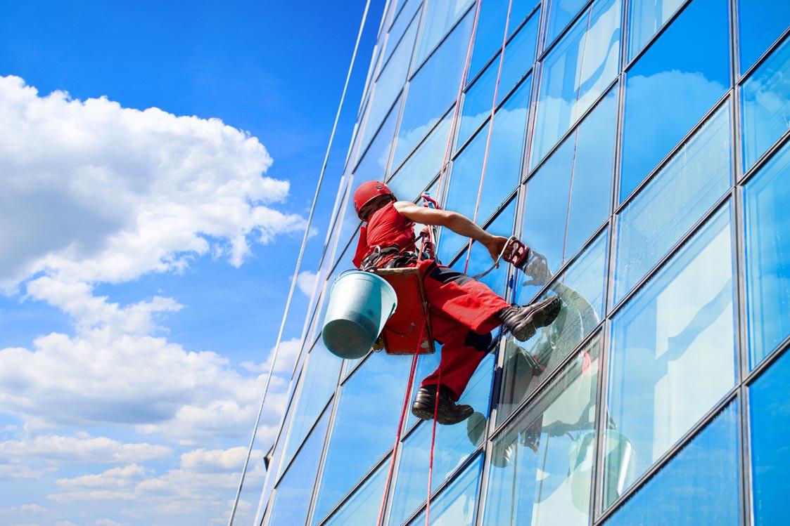 Gebäudereiniger bei der Arbeit an der Außenfassade eines Hochhauses