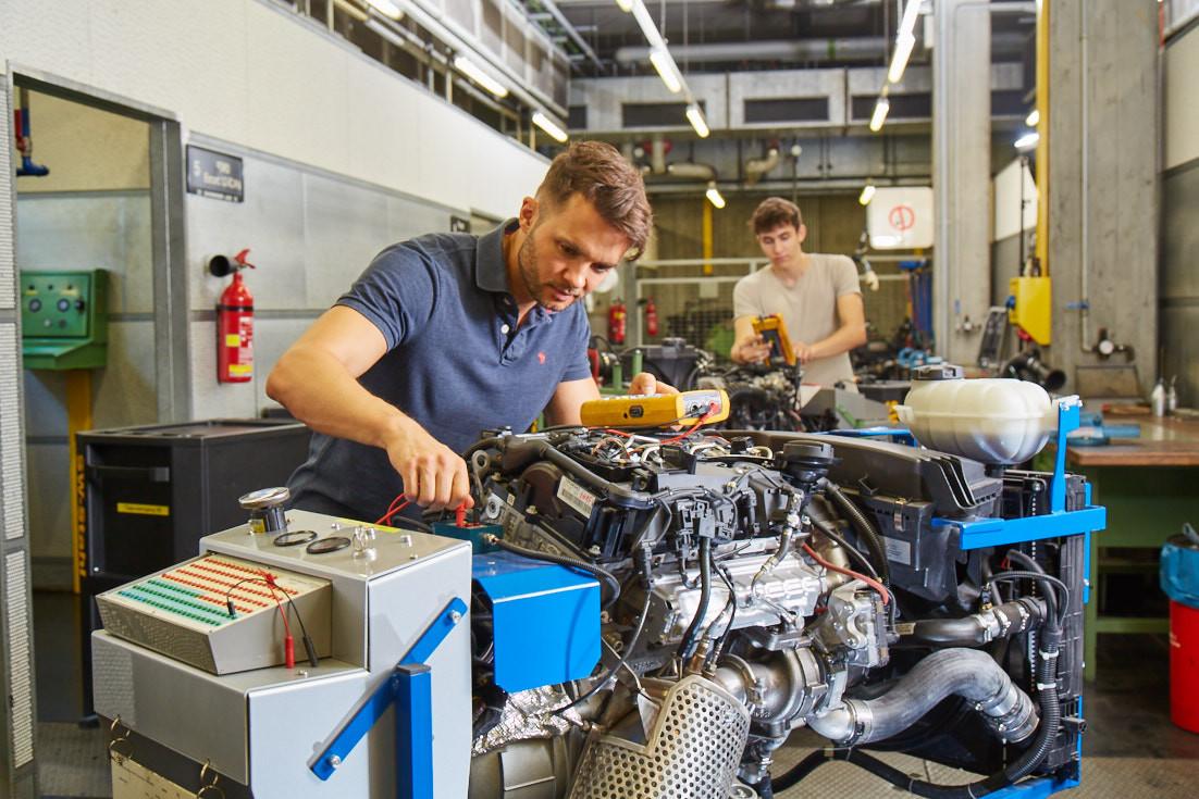 Kraftfahrzeugtechniker bei der praktischen Arbeit in der Werkstatt