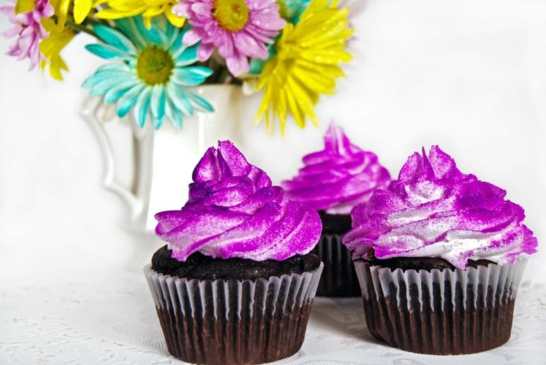 Cupcakes mit Schokolade und Glitzer-Topping vor passender Blumendekoration